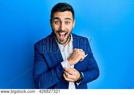Young hispanic businessman wearing business jacket putting on shirt button smiling and laughing hard out loud because funny crazy joke.