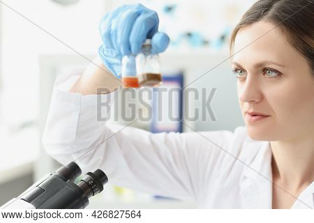 Woman Scientist Chemist Holding Glass Jars With Medicine In Front Of Microscope