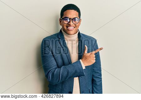 Young handsome hispanic man wearing elegant clothes and glasses cheerful with a smile of face pointing with hand and finger up to the side with happy and natural expression on face