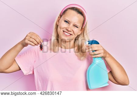 Beautiful caucasian blonde woman holding cockroach and pesticide sprayer winking looking at the camera with sexy expression, cheerful and happy face.