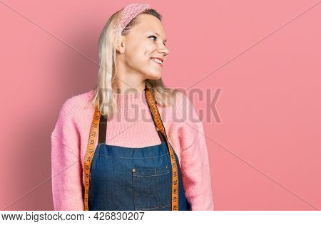 Young caucasian woman dressmaker designer wearing atelier apron looking to side, relax profile pose with natural face and confident smile.