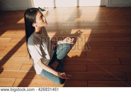 Asian Woman Doing Yoga And Zen Like Meditation Lotus Pose In Casual Wear At Indoor Living Room Apart