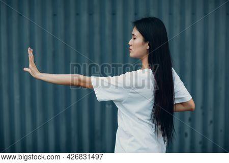 Asian Young Woman Doing Qigong Exercise Summer Outdoor. Hand Forward Selective Focus
