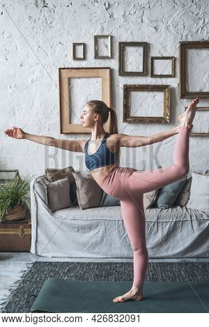 Full Length Vertical Shot Of Young Fit Healthy Woman Standing In Natarajasana Yoga Pose In Living Ro