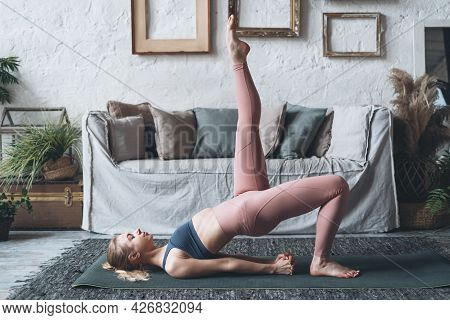 Young Sporty Fit Woman Lying On Yoga Mat In Living Room And Doing Fitness Exercise For Buttocks And