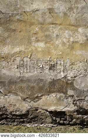Old Yellow Plaster And Brick Wall With Green Grass Underneath. Architectural Detail Background.
