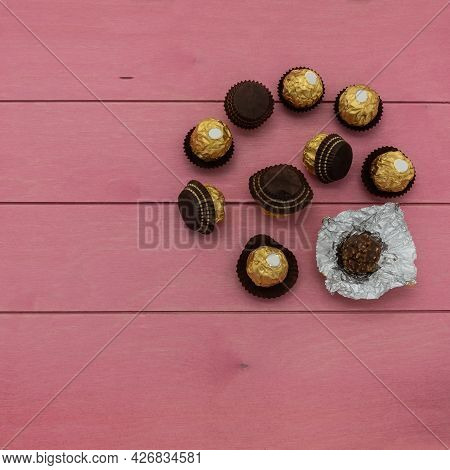 Spherical Chocolates Wrapped In Golden Foil Are Scattered On A Pink Wooden Table. One Candy Is Unwra