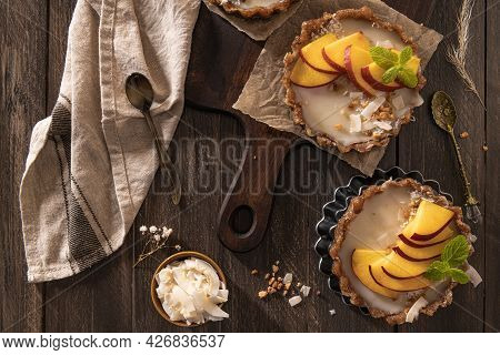 Nectarine Vegan Tarts With Grated Coconut And Crunchy Peanuts. Date, Walnut, Almond And Hazelnut Bas