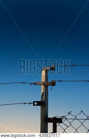 Two Rows Of Barbed Wire And A Fence Post, With Blue Sky In The Background. Immigration, Escape Or Fr