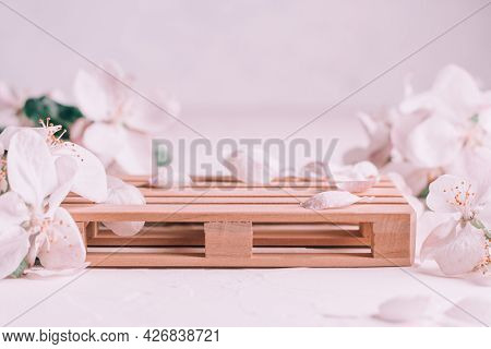 Wooden Podium In Form Of Pallet On Light Plaster Surface With Apple Flowers. Podium, Pedestal Or Sta