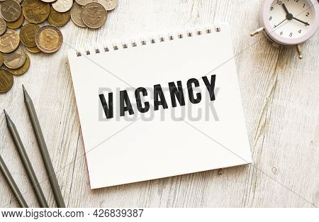 Vacancy Text On A Sheet Of Notepad. Coins Are Scattered, Pencils On A Gray Wooden Background. Financ