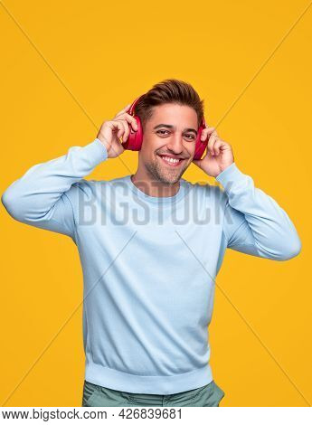 Optimistic Young Bearded Male In Casual Clothes And Wireless Headphones Having Fun And Enjoying Good
