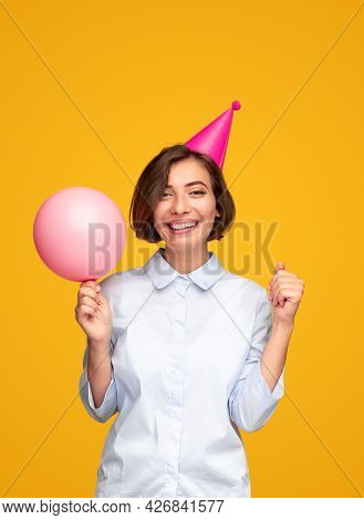 Optimistic Young Woman In Party Hat Smiling For Camera And Raising Hands With Balloons While Celebra