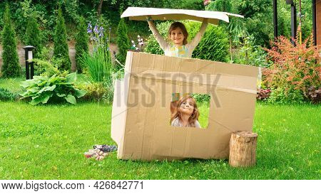 Children Built A Cardboard House Out Of A Box And Play In It. Real Estate Purchase Concept. Moving T