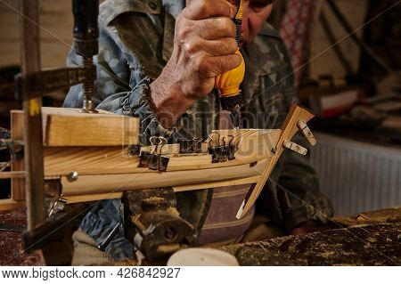Carpenter In Action, Lifestyles, Hobby Concepts. Craftsman Sticking Wooden Details On A Sailboat In