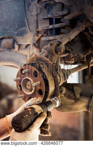 Male Hands In Gloves Use A Power Tool To Clean Rust On The Wheel Hub Of A Car. In The Garage, A Man