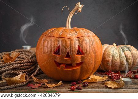 Halloween Pumpkin, Jack's Head On A Dark Background With Foliage And Blown Out Candles. A Traditiona