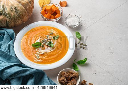 Autumn Pumpkin Soup In A White Plate On A Gray Background With Pumpkin, Spices And Rye Crackers. Hor