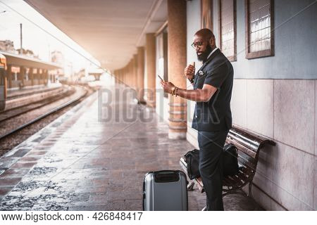 An Elegant Black Businessman Is Standing With His Baggage Bags On An Empty Railrway Platform Of A Ra