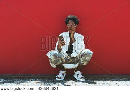 A Fancy Young African Female Is Squatting Near A Red Wall, Making Faces And Texting Via A Smartphone