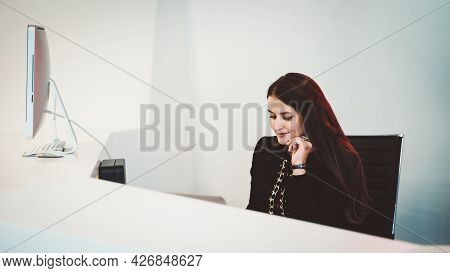 A Charming Female Receptionist With Long Hair Is Working On Her Netbook While Sitting At The Table O