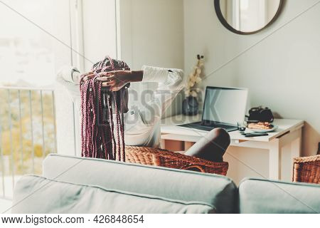 View From Behind Of A Black Woman Fixing Her Long Braided Hair With Hands While Sitting In The Kitch