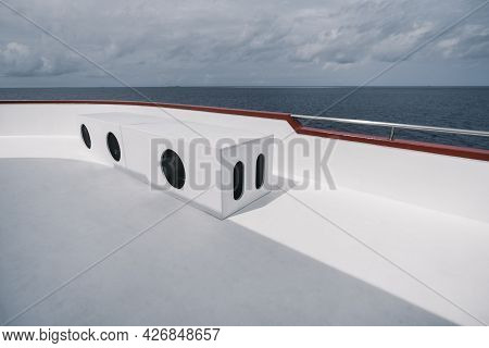 View From The Upper Deck Of A Safari Boat With A Rectangular Box Bench With Three Round Holes From T