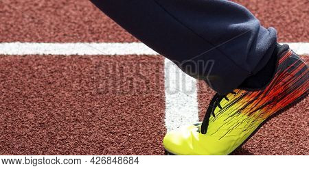 The Leg And Foot Of A Sprinter Runner Wearing A Yellow, Red And Black Spiked Shoe Running On A Red T