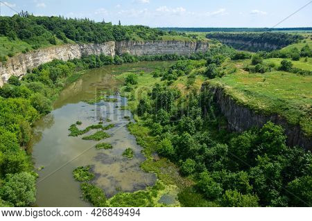 View Of The Former River That Has Become A Swamp. The Sides Are Overgrown With Trees. Rocky Cliffs O