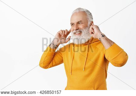 Handsome Senior Man Listen Music On Wireless Earphones And Smiling, Looking Aside At Logo. Hipster O