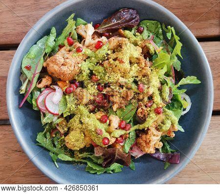 Healthy Salad Of Cauliflower, Reddish, Rocket, Beetroot And Pomegranate Seeds