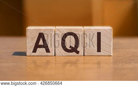 Aqi Abbreviation Of Air Quality Index Text On Wooden Cubes On Orange Wall Background.