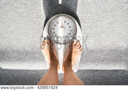 Weighing Scale Weight Check And Measure. Lady Standing After Workout