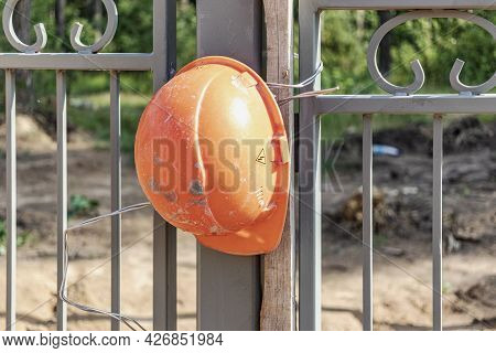 A Working Construction Helmet Hangs On The Fence. Completion Concept. Builders Protest About Low Wag