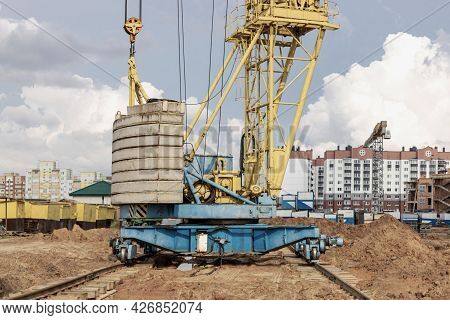 Tower Crane On Rails Close-up At The Construction Site Against The Background Of The Cloudy Sky. Clo