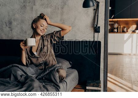 Young Relaxed Woman In Stylish Home Suit Waking Up With Cup Of Coffee In Bed In Cozy Stylish Bedroom