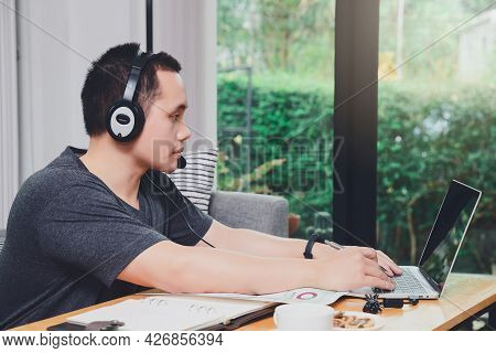 Businessman Video Call With Clients On Laptop In Home Office. Man Wear Headphone Video Calling Or Di