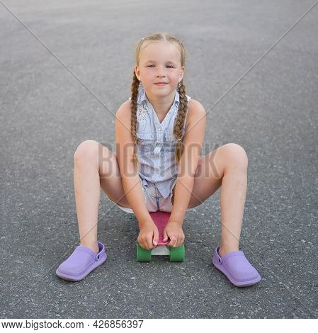 Cute Little Preteen Girl With Two Pigtails Sits On Skateboard