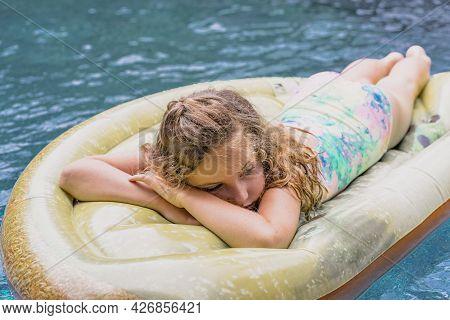 Young Girl In Fashionable Swimwear Sunbathing On Swimming Pool On The Inflatable Mattress In Summer.