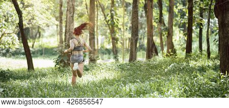 Young Woman Runner Listening Music On Headphones While Running On Tropical Rainforest Trail In The M