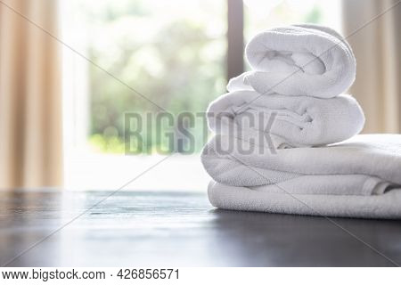 Roll Up Of White Towels On Table With Copy Space On Blurred Room Background. For Product Display Mon