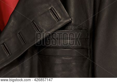 Close Up Detail Of Black Leather Steampunk Jacket, Showing Button Holes And Breast Pockets And Red L