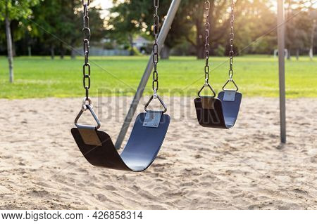Playground Without Children In The Local Public Park, Set Of Swings On Chains With Sand Underneath,