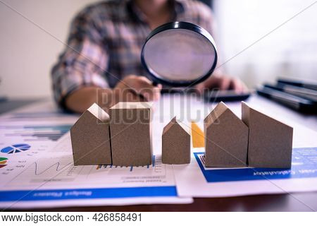Real Estate Or House Appraisal Using Calculator And Holding A Magnifying Glass Over The Model Of A W
