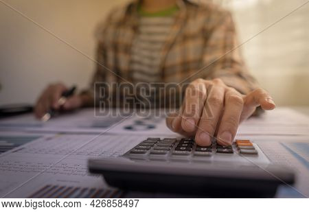 Accountant Or Young Entrepreneur Working With Calculator And Calculate Profit Report, Income Statist