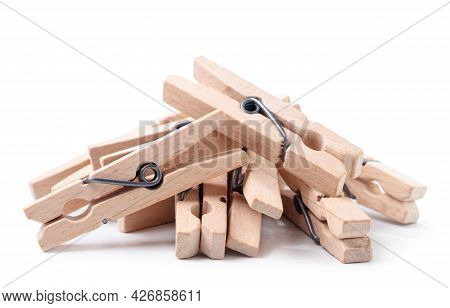 A Pile Of Wooden Clothespins Close-up On A White Background. Isolated