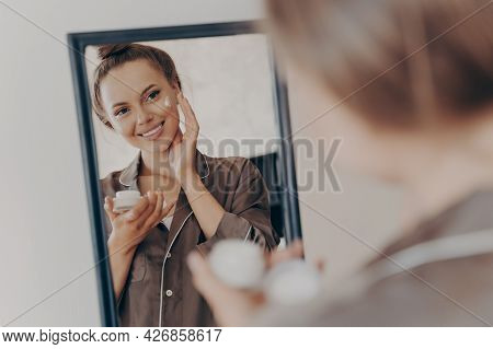 Reflection In Mirror Of Beautiful Woman In Silk Pajama Smiling While Applying Face Cream For Deeper