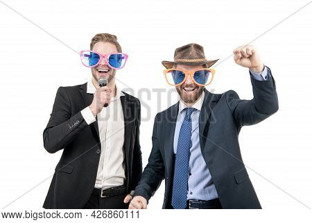 Happy Employees Have Fun Singing Karaoke In Funny Glasses And Formalwear, Corporate Party
