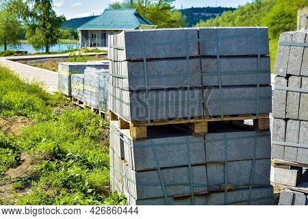 Pallets With Gray Paving Slabs In Park Area On River Bank. Plastic Packaging Protects The Tile From