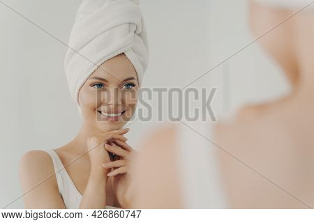 Positive Healthy Young Woman Smiling While Applying Facial Cream Reflecting In Mirror, Happy Attract